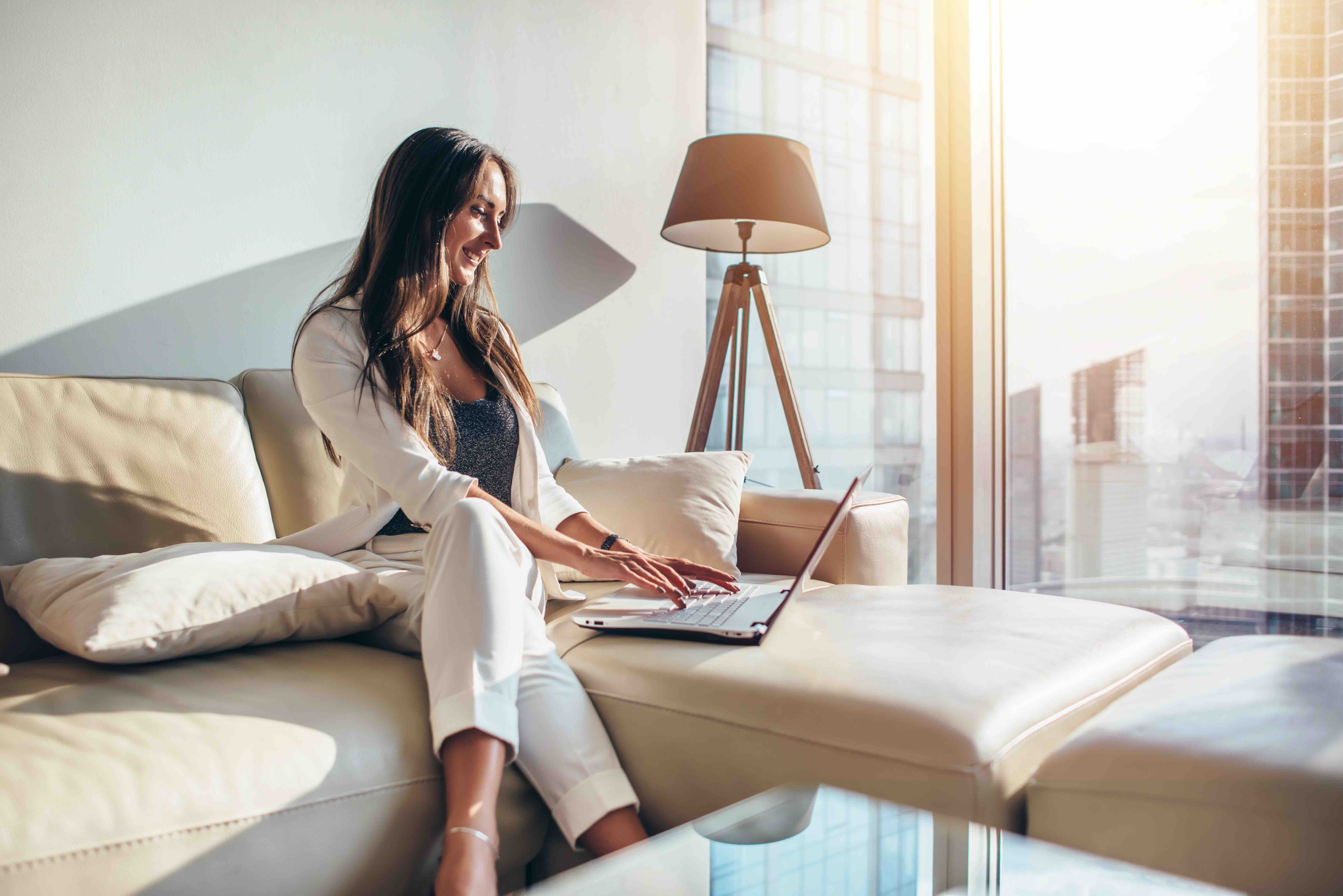 Elegant young female business woman using a laptop sitting on a sofa at home.